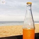 Bottle of orange juice on the beach